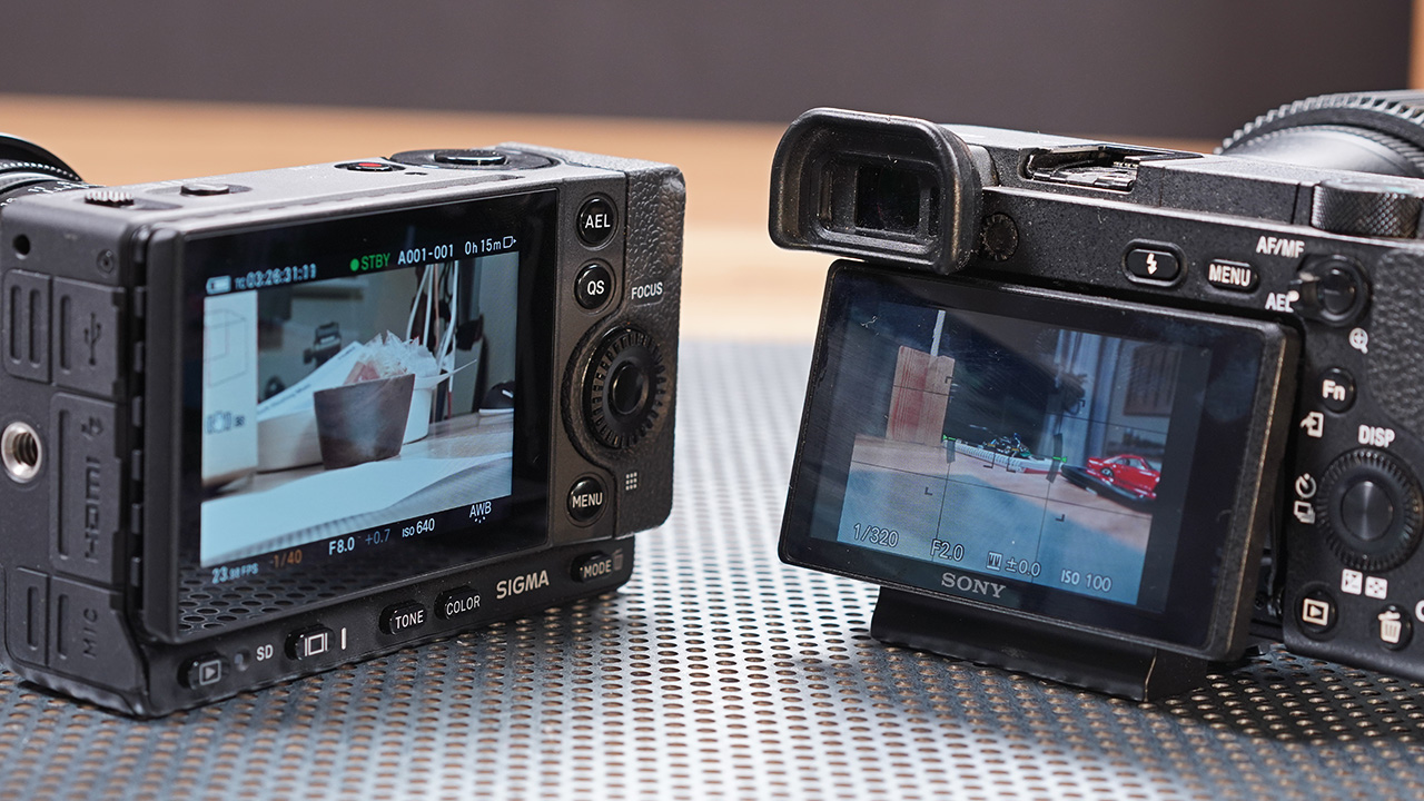 No flip/articulated LCD and no EVF (compared to the Sony A6500 on the right)